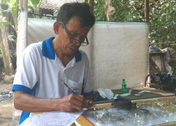 Pelukis kaca sedang melukis di DEsa Nagasepaha, Buleleng