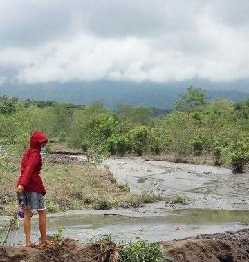 Seorang anak menonton lahar dingin di sebuah sungai di Karagasem. /Foto: Kardian Narayana
