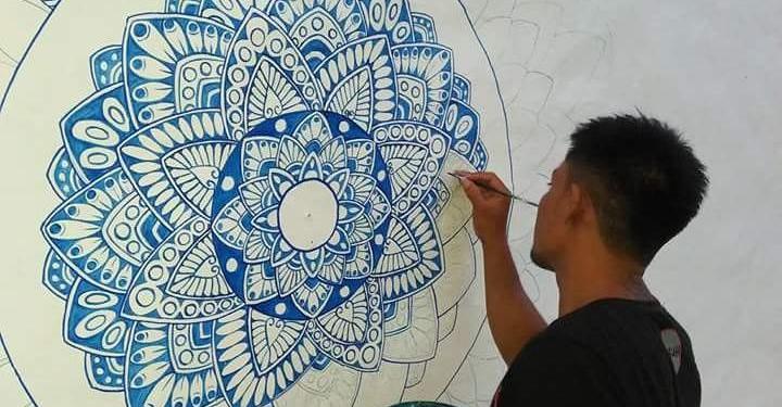 Sumadi melukis di dinding. /Foto: Santana