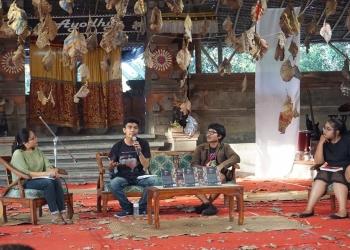 Putu Supartika pegang mik saat bicara soal sastra dalam media massa di Bali